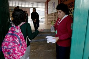 Profesora aplica gel antibacterial a alumnos en la entrada de una escuela en la alcaldía Cuauhtémoc, en marzo pasado. Foto María Luisa Severiano.